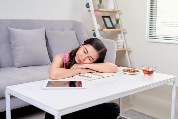 Vermoeide overwerkte vrouw die aan het rusten was terwijl ze aan het werk was met het schrijven van notities