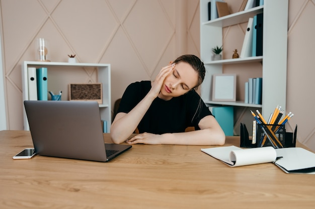 Vermoeide overwerkte zakenvrouw op de werkplek op kantoor die gestrest is