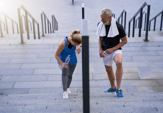 Vermoeide paar man en vrouw van middelbare leeftijd in sportkleding die de trap oploopt na het sporten