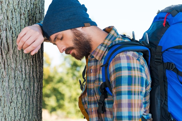 Vermoeide reiziger. zijaanzicht van vermoeide jongeman met rugzak die tegen de boom leunt en de ogen gesloten houdt