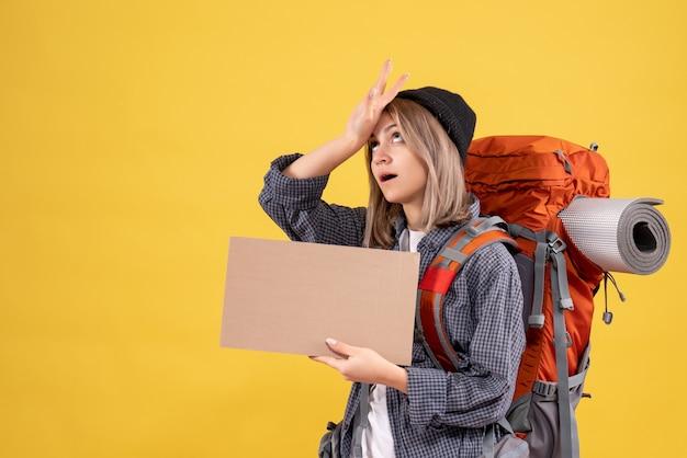 Vermoeide reizigersvrouw met rugzak die karton houdt