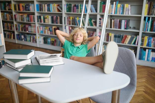 Vermoeide schooljongen zit aan tafel met gesloten ogen en zijn voeten op het bureau