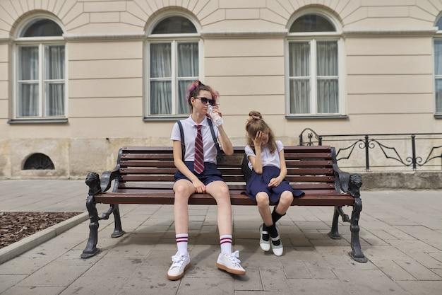 Vermoeide schoolkinderen die op bank zitten. twee meisjes zusters tiener en basisschool student
