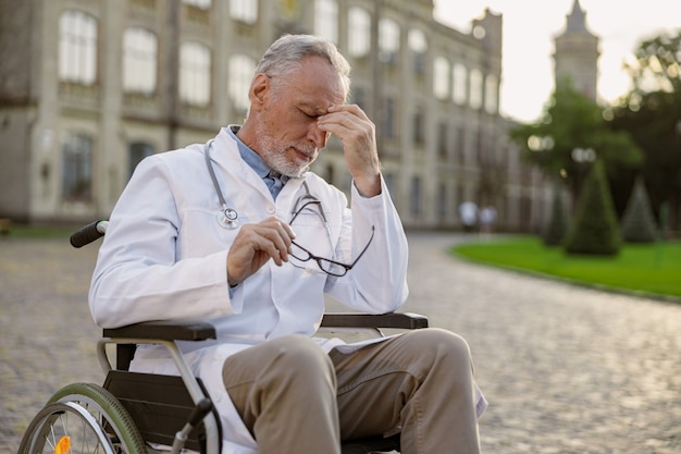 Vermoeide senior gehandicapte mannelijke arts in rolstoel met laboratoriumjas die zijn bril afdoet en heeft