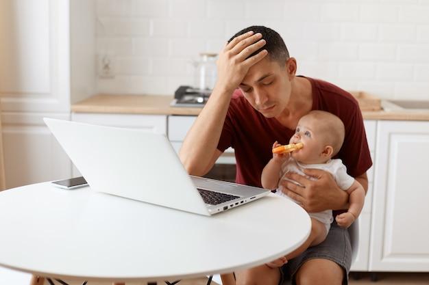 Vermoeide, slaperige knappe freelancer-man met een bordeauxrood r-shirt, poserend in een witte keuken, zittend voor een laptop met baby in handen, met vreselijke hoofdpijn.