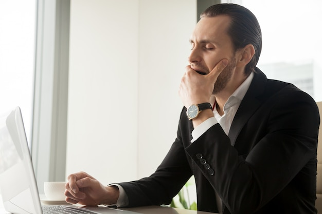 Vermoeide slaperige zakenman die voor laptop geeuwt