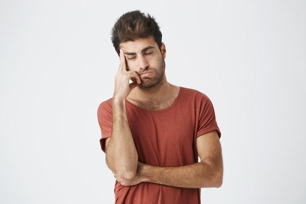Vermoeide spaanse gebaarde mens die de rode hand van de t-shirtholding op voorhoofd dragen kijkend zwaar hebbend hoofdpijn na conflictsituatie op het werk. mensen, stress en migraine.