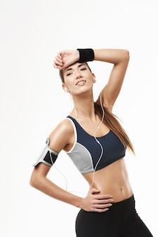 Vermoeide sportieve vrouw die in hoofdtelefoons in zijholdingshand kijken op voorhoofd op wit.
