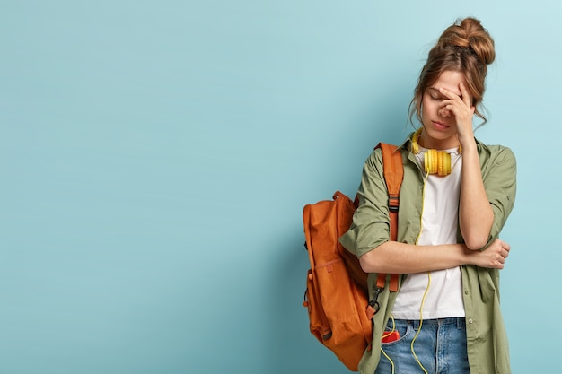 Vermoeide studente heeft een slaperige uitdrukking, probeert zichzelf op te frissen met muziek in koptelefoons, draagt een rugzak, draagt vrijetijdskleding