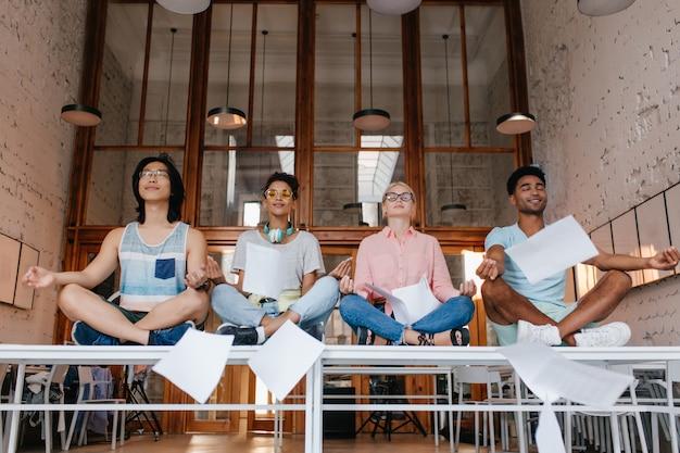 Vermoeide studenten die samen mediteren en documenten weggooien. indoor portret van meisjes en jongens zittend op witte bureaus in lotus houding met gesloten ogen en zachtjes glimlachen.