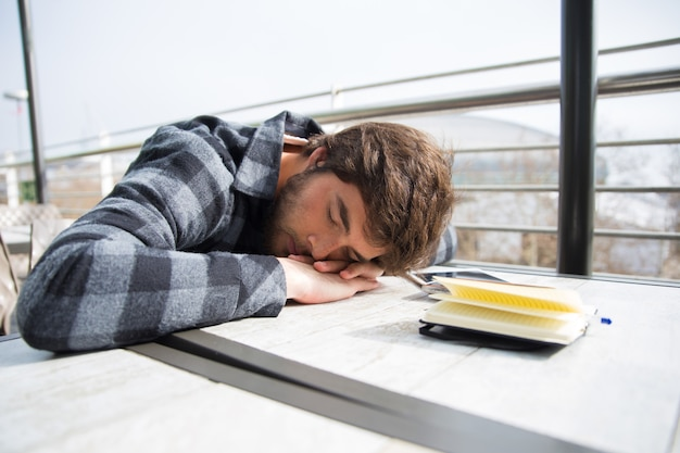 Vermoeide studentenslaap met zijn hoofd rustte op lijst