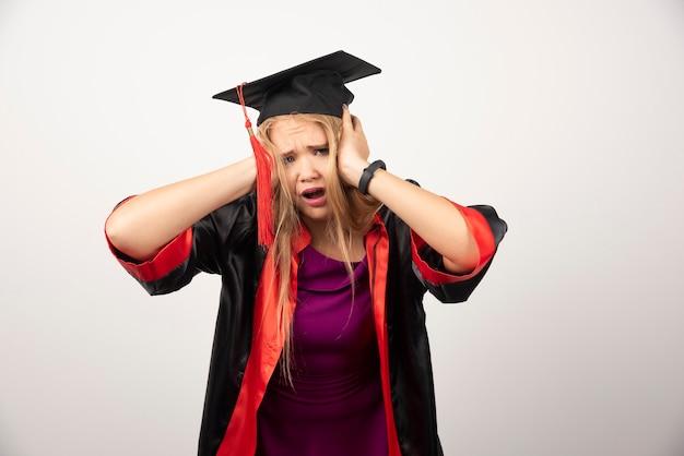 Vermoeide studentenvrouw die haar oren op wit behandelen.