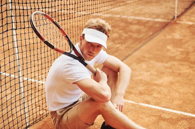 Vermoeide tennisser in sportieve kleding is buiten op het veld leunend op het net.