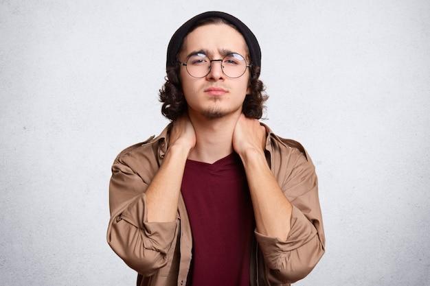 Vermoeide tiener met fris haar, heeft pijn in de nek, gekleed in een rood casual t-shirt, een bruin shirt en een zwarte pet