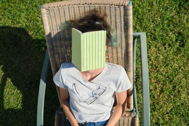 Vermoeide tienerstudent in slaap op zonnebank met boek. slapend meisje op zonnige dag, op groen gazon in tuin. rust, training, gezonde slaap overdag, jeugd Premium Foto