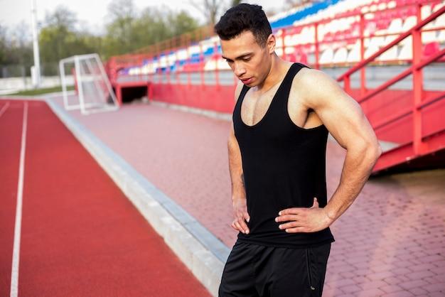 Vermoeide uitgeputte mannelijke atleet die zich op stadion bevinden