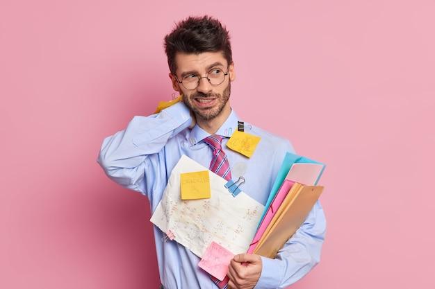 Vermoeide, uitgeputte werknemer heeft nekpijn, houdt mappen vast en draagt shirt met bijgevoegde plakbriefjes geschreven informatie poses