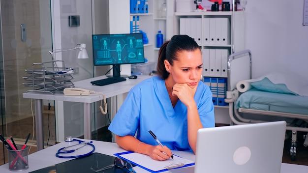 Vermoeide verpleegster-dokter die een bril afzette, rustende ogen bleef naar het pc-scherm staren. arts in de geneeskunde uniforme schrijflijst van geraadpleegde, gediagnosticeerde patiënten, die onderzoek doen.