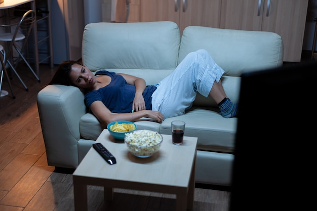 Vermoeide, verveelde, ongelukkige huisvrouw met afstandsbediening liggend op de bank lachend en snacks etend. eenzame dame in pijamas genieten van de avond zittend op een comfortabele bank televisie kijken.