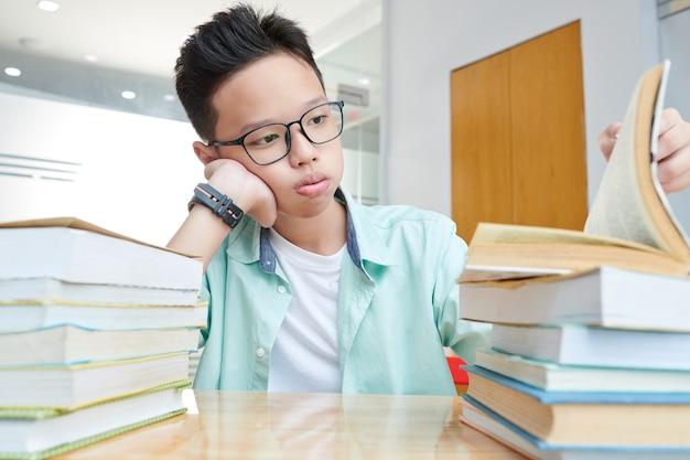 Vermoeide vietnamese schooljongen die stapels boeken op zijn bureau bekijkt die hij moet lezen ter voorbereiding op het examen