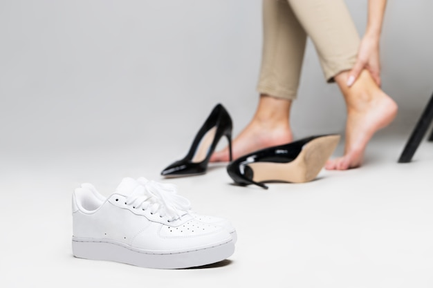 Vermoeide vrouw aanraken van haar enkel, pijn in het been vanwege ongemakkelijke schoenen, pijn in voeten, hoge hakken dragen na het lopen, focus op comfortabele sneakers