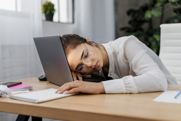 Vermoeide vrouw die haar hoofd op laptop rust