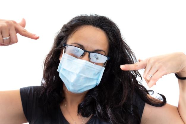 Vermoeide vrouw die het zwarte masker van het t-shirtgezicht en beslagen bril draagt op witte backgroundcr