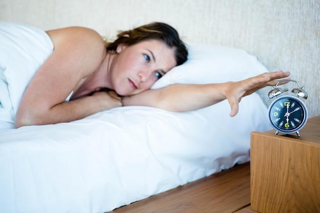 Vermoeide vrouw die in bed ligt en haar alarm uitstelt
