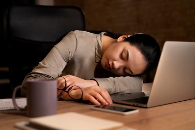 Vermoeide vrouw die laat op kantoor werkt
