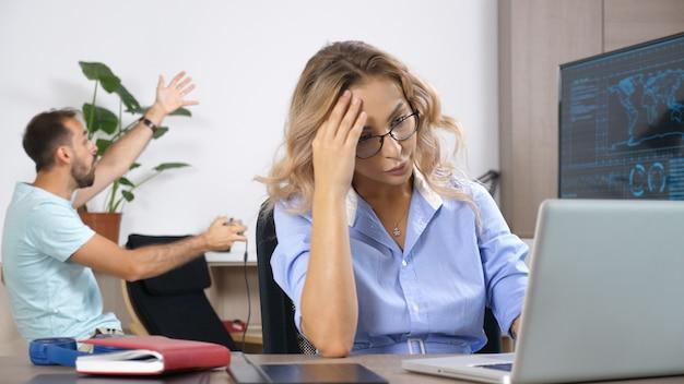 Vermoeide vrouw die op de computer werkt terwijl haar man op de achtergrond videogames speelt