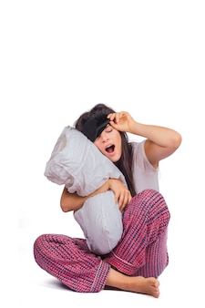 Vermoeide vrouw die slaapmasker, pyjama draagt en hoofdkussen houdt.