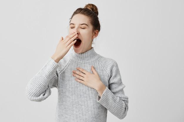 Vermoeide vrouw geeuw die open mond behandelt met de behoefte van de handrust. jonge vrouwelijke werknemer die slaperig hoofd is, kan niet wakker worden met slapeloosheid. kettingreactie