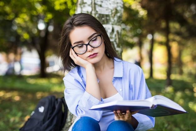 Vermoeide vrouw in glazen studies tegen zomer groen park.