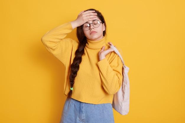 Vermoeide vrouw in stijlvolle kleding poseren geïsoleerd over gele muur, ogen gesloten houden, haar voorhoofd aanraken, ziet er moe en uitgeput uit, dame met eco-tas.