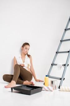 Vermoeide vrouw klaar om muur in haar huis te schilderen. mooie vrouw met een kwast