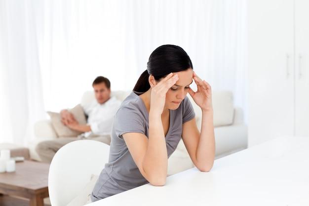 Vermoeide vrouw met een hoofdpijn zittend aan een tafel in de woonkamer