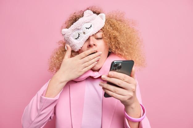 Vermoeide vrouw met krullend haar voelt zich uitgeput na een zakelijke bijeenkomst die heel laat informatie in smartphone-covers controleert mond geeuwen draagt slaapmasker reiskussen om nek fomal kleding