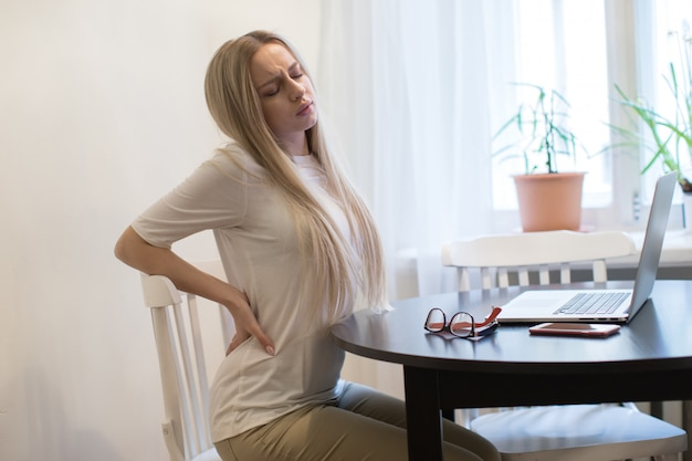Vermoeide vrouw met pijn, spierpijn of chronische zenuwpijn in haar rug na overwerk op laptop.