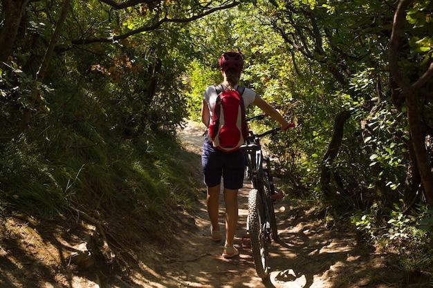 Vermoeide vrouw met rugzak en helm die naast haar fiets in het bospad van strunjan, slovenië loopt