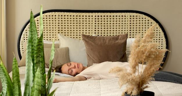 Vermoeide vrouw na het werk. valt op bed. zachte matras. slaap