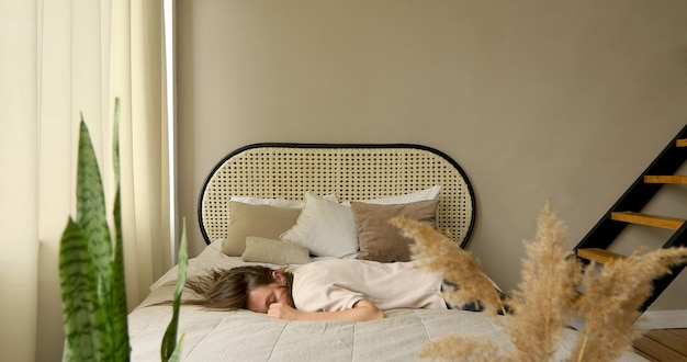 Vermoeide vrouw na het werk. valt op bed