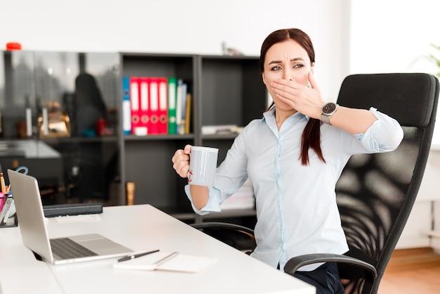 Vermoeide vrouw op kantoor op de werkplek geeuwen en wakker worden