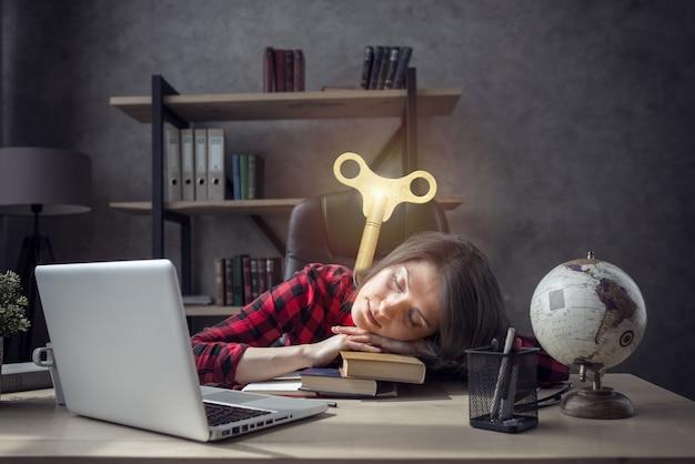 Vermoeide vrouw slaapt over de boeken heen en heeft een lading nodig