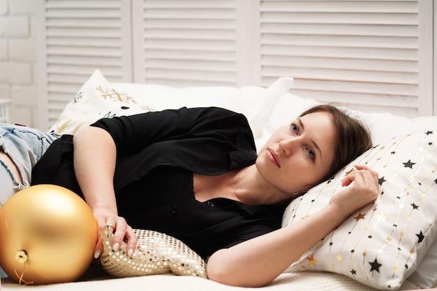 Vermoeide vrouw valt in slaap liggend op het bed. uitgeput en viel zonder krachten neer. gooide alleen in het nieuwe jaar. eenzaamheid in een bed is niemand aanwezig. moe van kerstmis. vakantie alleen zonder familie