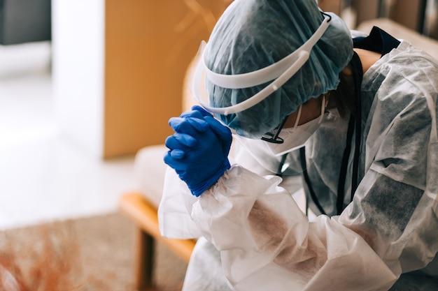 Vermoeide vrouw verpleegster ziekenhuis werknemer chirurg arts in beschermende kleding op zoek verdrietig na een zware werkdag of een operatie.