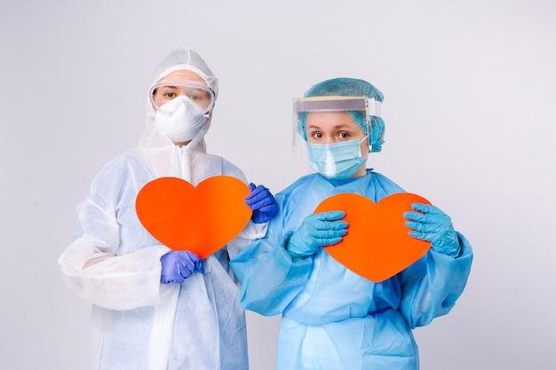 Vermoeide vrouwelijke artsen in virusbescherming houden papieren rode harten in handen