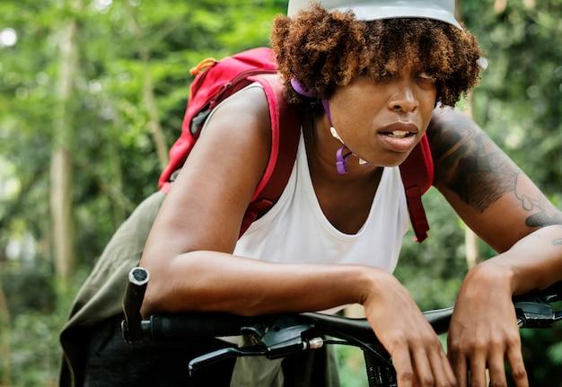 Vermoeide vrouwelijke fietser in het bos