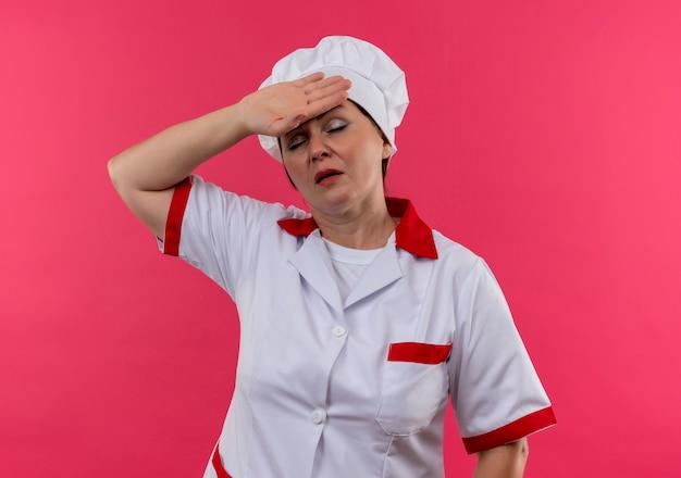 Vermoeide vrouwelijke kok van middelbare leeftijd in eenvormige chef-kok die hand op voorhoofd zet