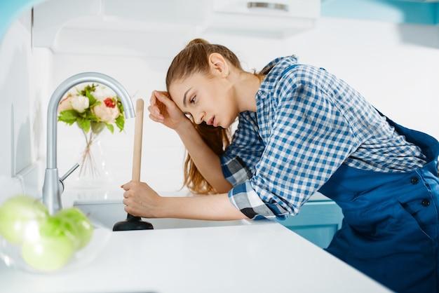 Vermoeide vrouwelijke loodgieter in uniform houdt zuiger vast, verstopping in de keuken. handywoman reparatie wastafel, sanitair service aan huis