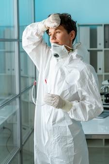 Vermoeide vrouwelijke medisch specialist in beschermend pak houden bril en zweet afvegen na moeilijk werk met coronaviruspatiënten